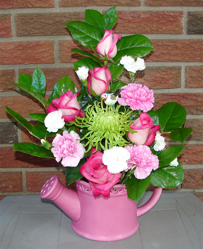 Assorted colourful flowers in a pink container