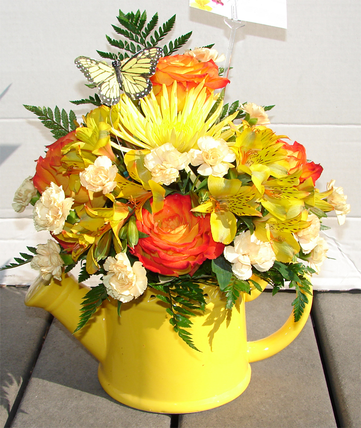 Assorted bright flowers in a yellow watering pot